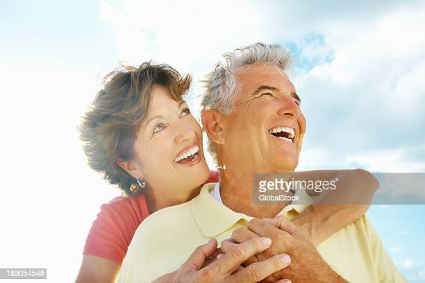 Cheerful woman embracing a senior man from behind against sky