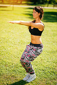 Cheerful woman exercises squats on sunny day in park