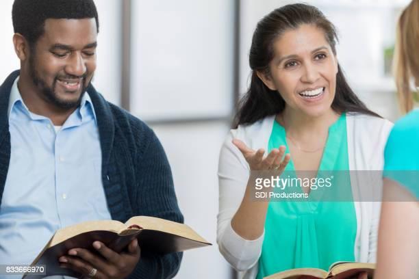 Cheerful woman facilitates office Bible study