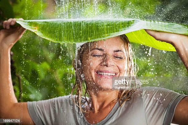 Cheerful woman having fun in jungle during tropical rain
