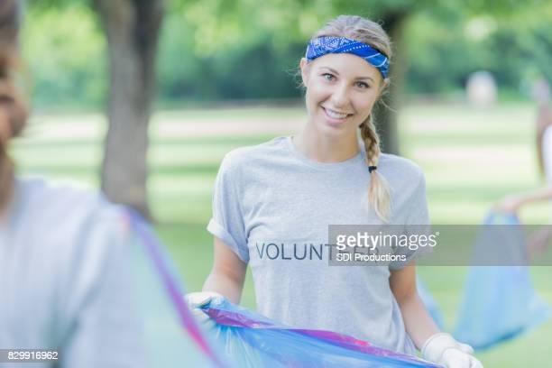 Femme joyeuse contribue avec le nettoyage de quartier