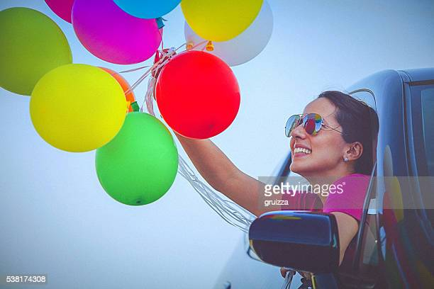 Cheerful woman holding colorful balloons, peeps out the car window