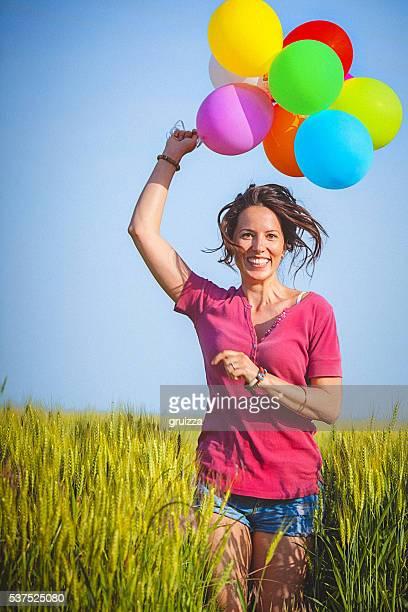 Cheerful woman holding colorful balloons, runs through wheat field