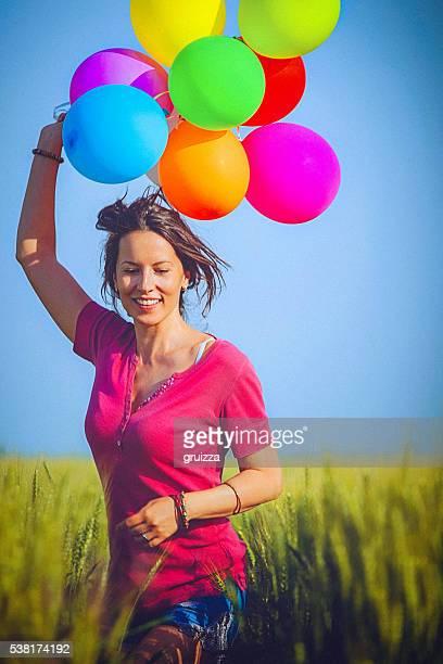 Joyeux femme tenant des ballons colorés, traverse le champ de blé