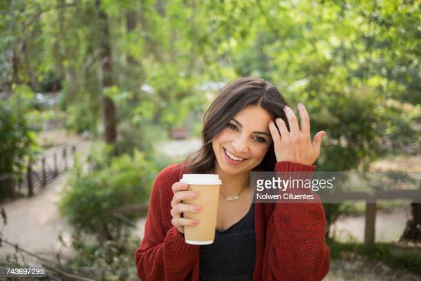 Cheerful woman holding disposable glass in park