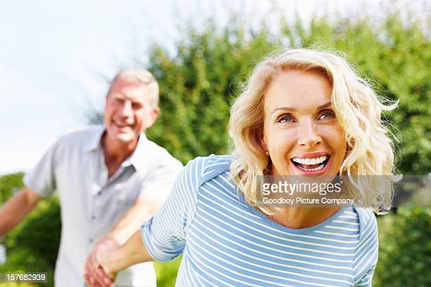 Cheerful woman holding hand of a senior man against sky