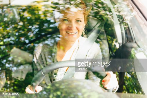 Cheerful woman holding steering wheel and driving car for Cheerful nature