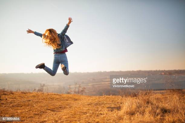 Cheerful woman jumping in the park