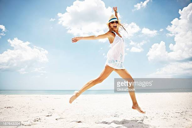 Cheerful woman jumping on a beach