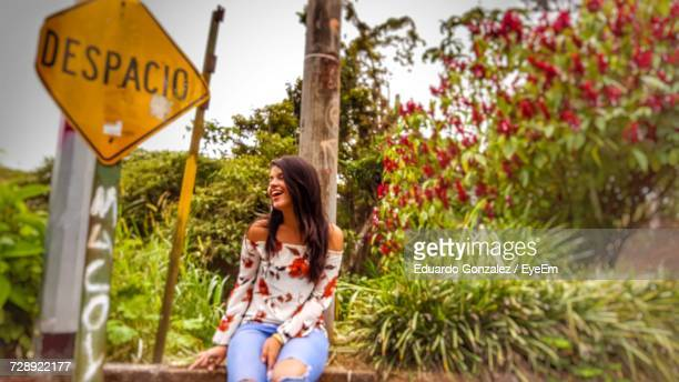 Cheerful Woman Laughing While Sitting On Retaining Wall By Road Sign Against Plants