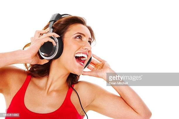Alegre mujer escuchando música con auriculares contra blanco