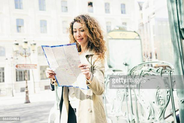 Cheerful woman looking at map out of subway station Paris