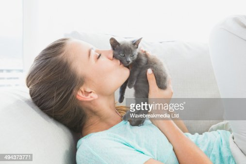 Cheerful woman lying on sofa kissing a grey kitten : Stock-Foto