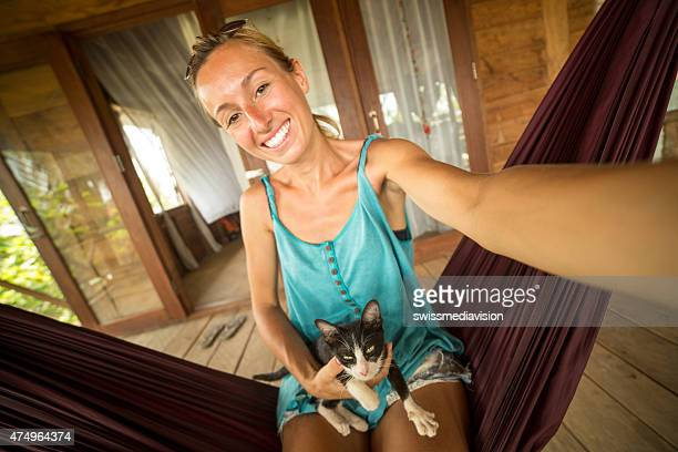 Cheerful woman on hammock with kitty taking selfie