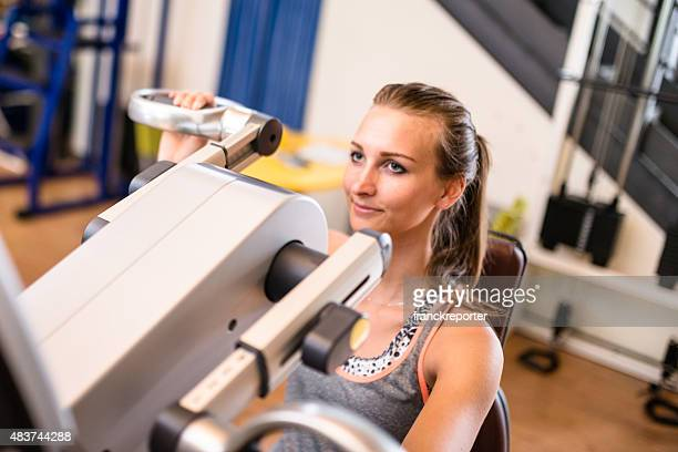 cheerful woman on the machine in the gym