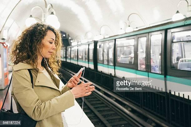 Femme heureuse au téléphone, sur fond de métro