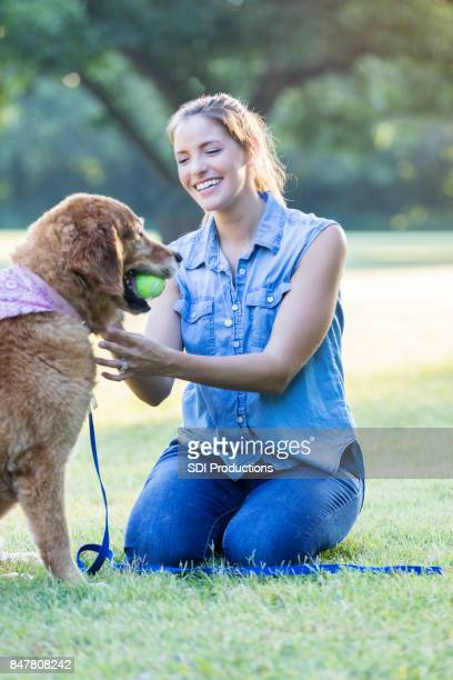 Cheerful woman plays with adorable dog in the park