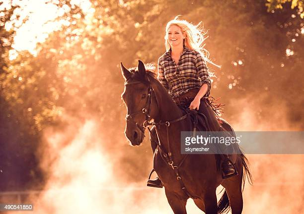 Cheerful woman practicing with her horse at sunset.