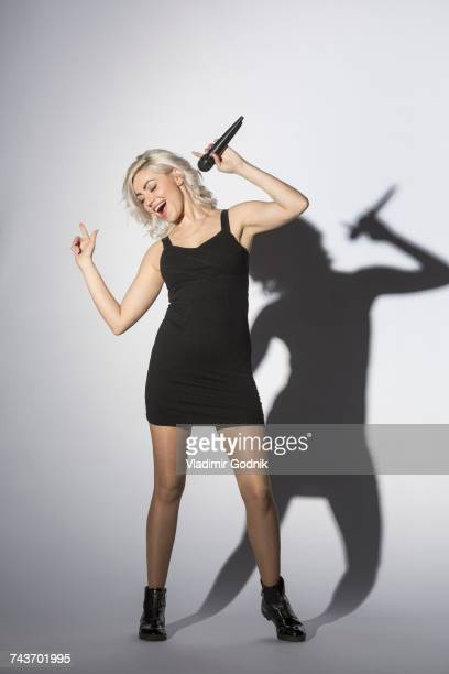 Cheerful woman singing with microphone while standing against white background