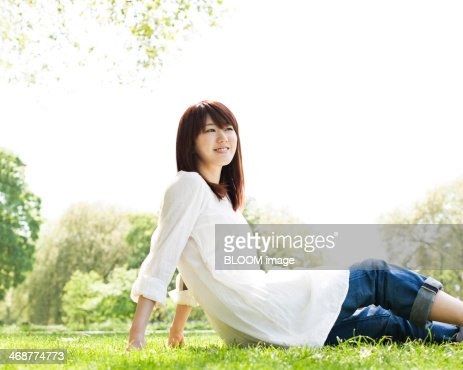 Cheerful Woman Sitting At Park : Stock Photo