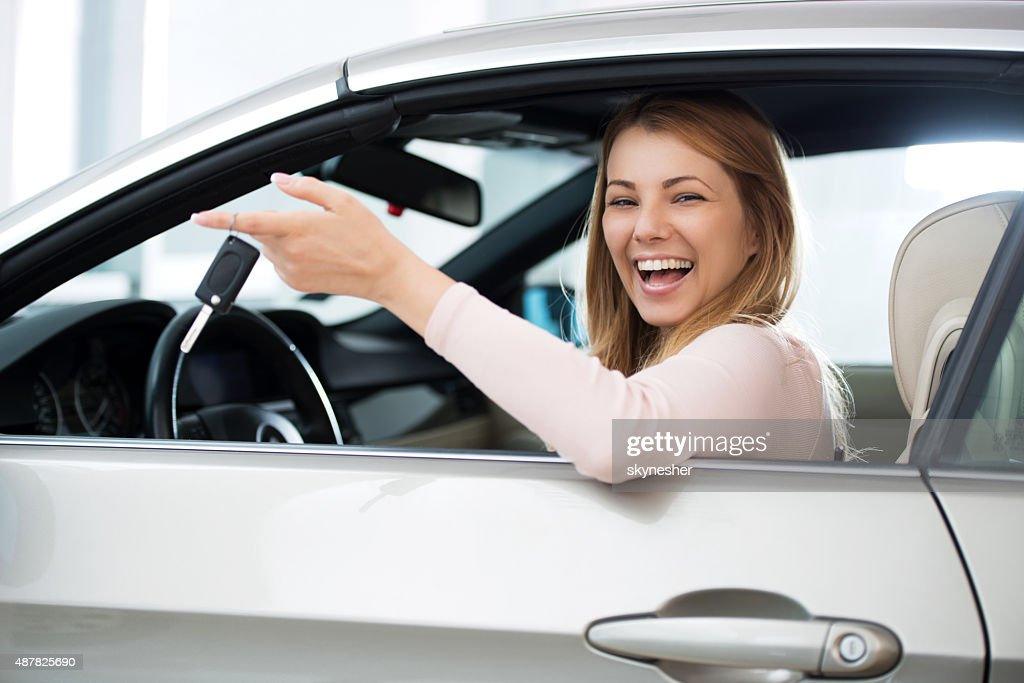 Cheerful woman sitting in a car holding new car keys. : Stock Photo