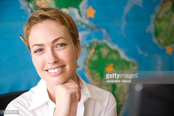 Cheerful woman sitting in front of world map