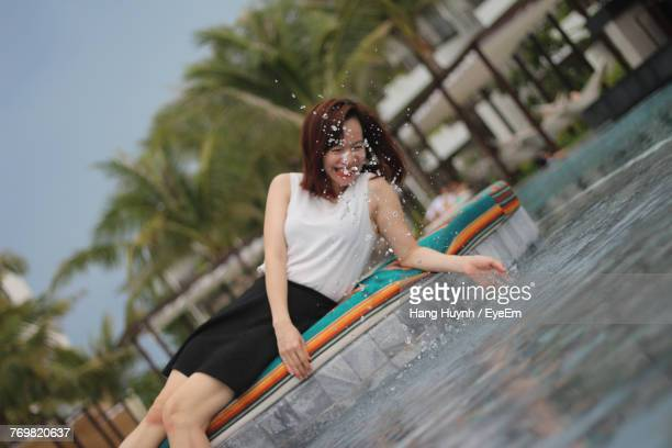 Cheerful Woman Splashing Water While Lying At Poolside