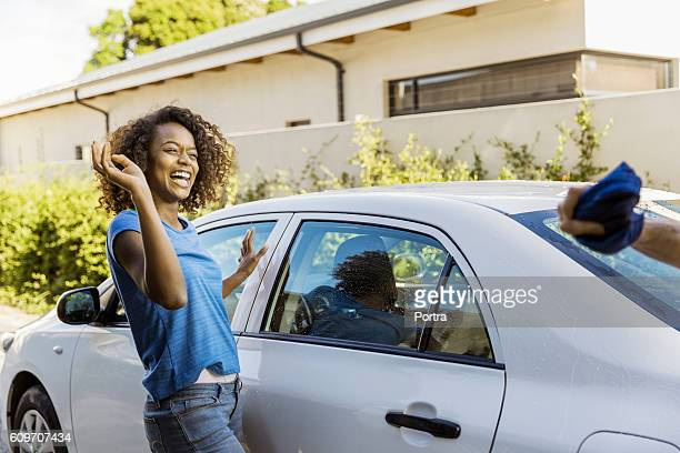 Cheerful woman standing by car in yard