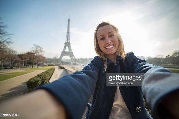 Cheerful woman takes selfie in Paris-Eiffel tower