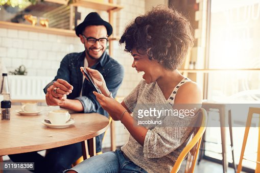 Cheerful woman using digital tablet with a friend at cafe : Stock Photo