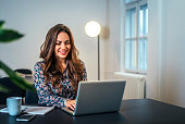 Cheerful woman using laptop at workplace.