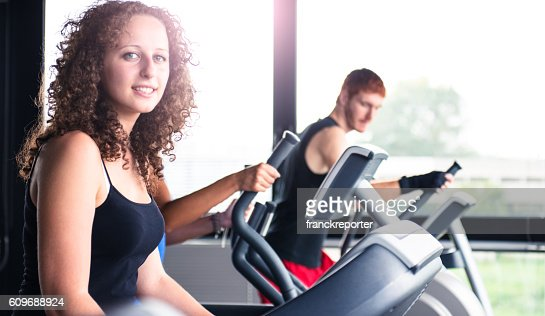 cheerful woman walking on the gym treadmill