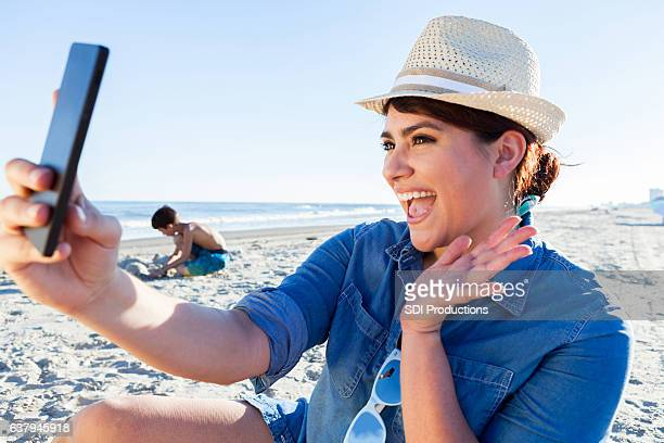 Cheerful woman waves while taking a selfie on the beach
