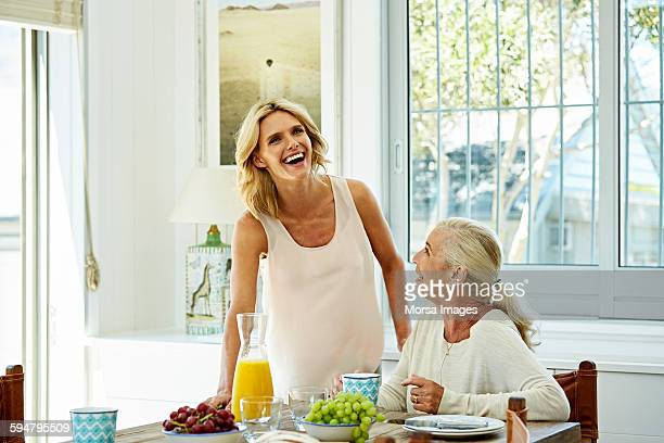 Cheerful woman with mother at table