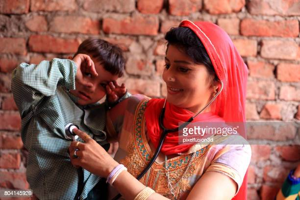 Cheerful women checking heartbeat of his son at home