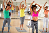 Attractive cheerful women dance at gym in colorful sportswear