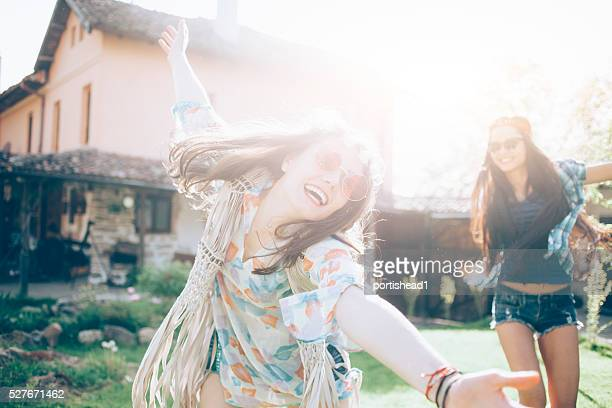 Cheerful women with daisies wreath dancing outdoor