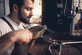 Side view smiling unshaven master smelling coffee grains while keeping them in ladle. He standing near industrial technical equipment. Factory concept
