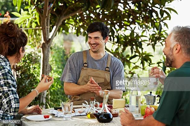 Cheerful workers having breakfast in yard