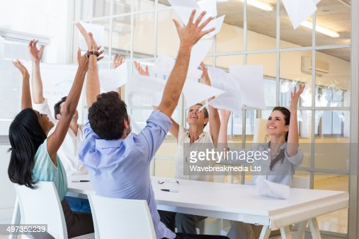 Cheerful workers throwing paper and smiling : Foto de stock