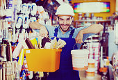 Cheerful workman boasting shopping in hardware store holding paint and tools