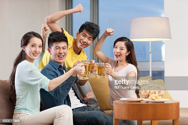 Cheerful young adults toasting with beer