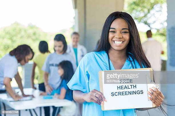 Cheerful young African American nurse promotes health fair