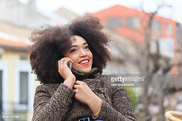 Cheerful young african woman talking on smart phone on street