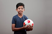Cheerful young boy holds a soccer ball in his hand