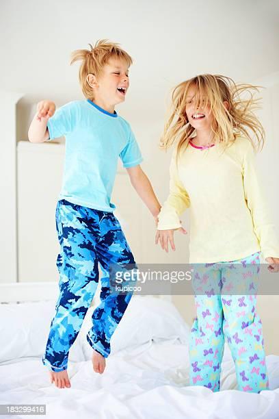 Alegre joven niño con su hermana salto de cama