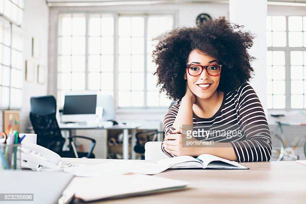 Fröhlich junge Geschäftsfrau sitzen auf Schreibtisch