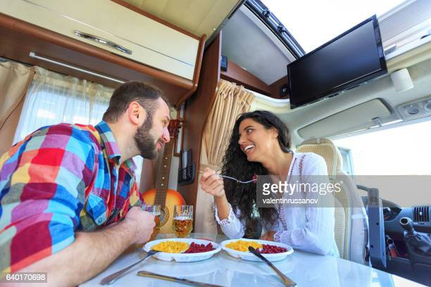Cheerful young couple eating inside of a camper