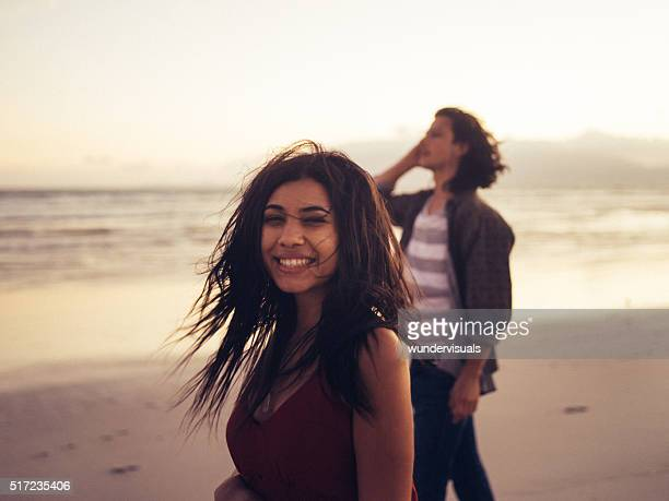 Cheerful young couple enjoying the beach at sunset