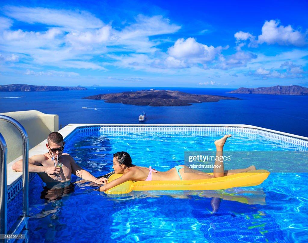 Swimming Pool Identification : Cheerful young couple having fun at swimming pool stock